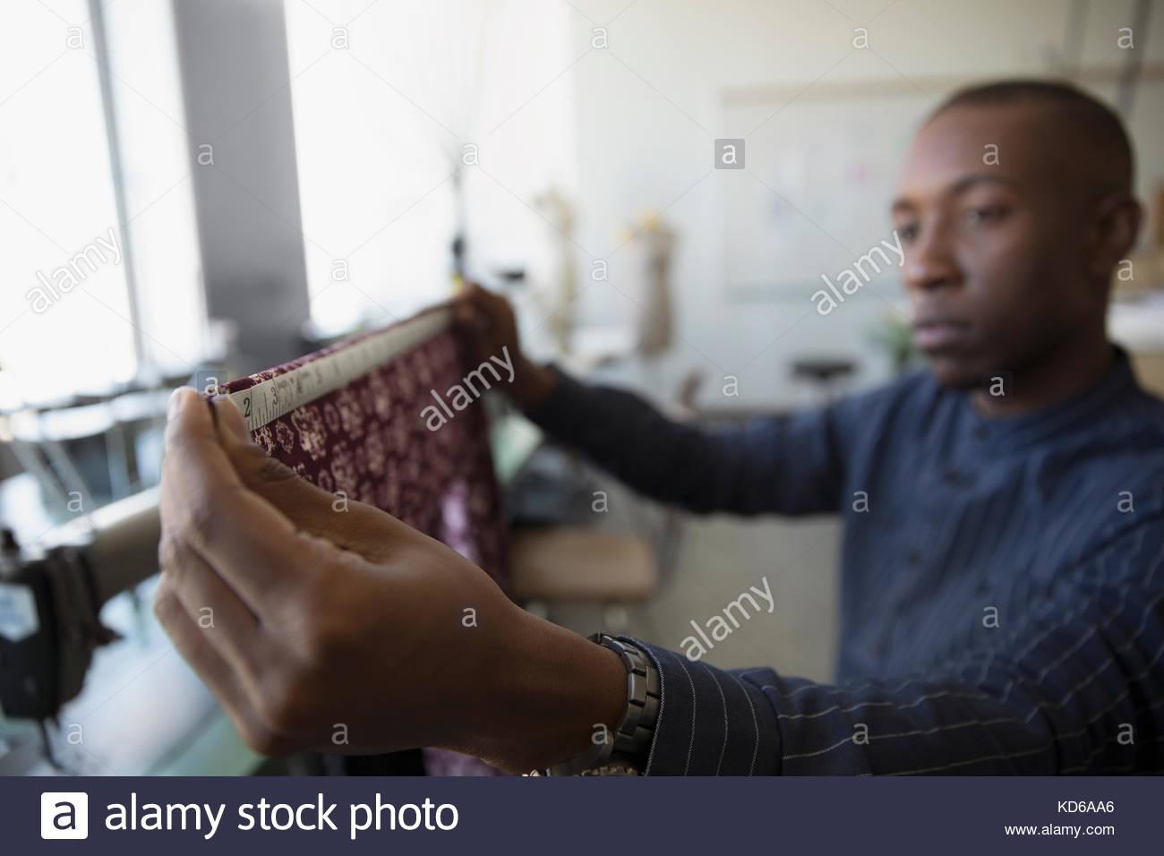 Focused male fashion designer measuring fabric in studio - Stock Image