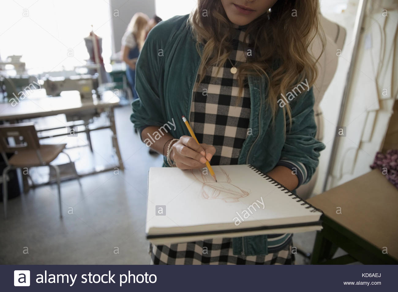 Female fashion design student sketching in notebook - Stock Image