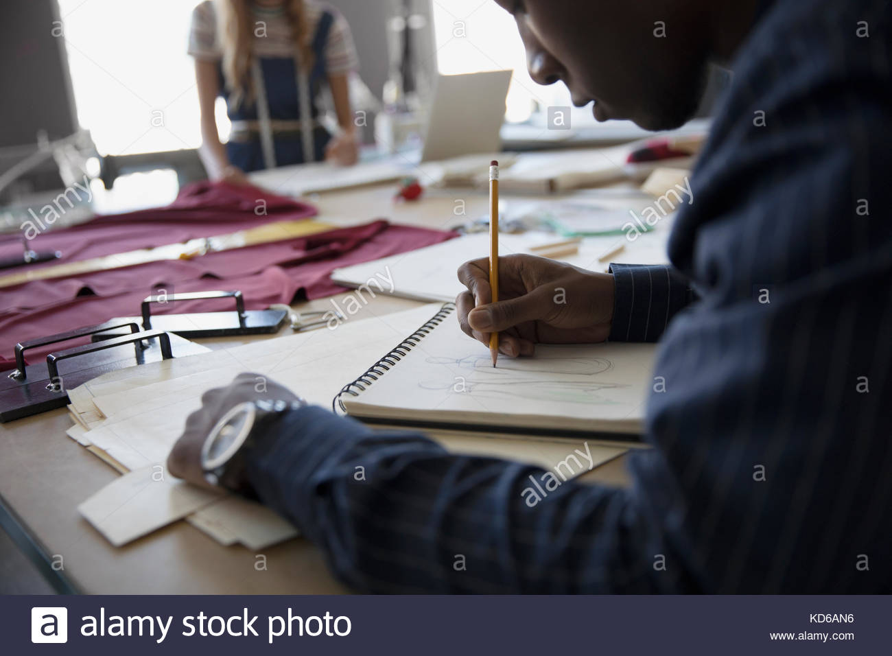 Male fashion design student sketching at workbench - Stock Image