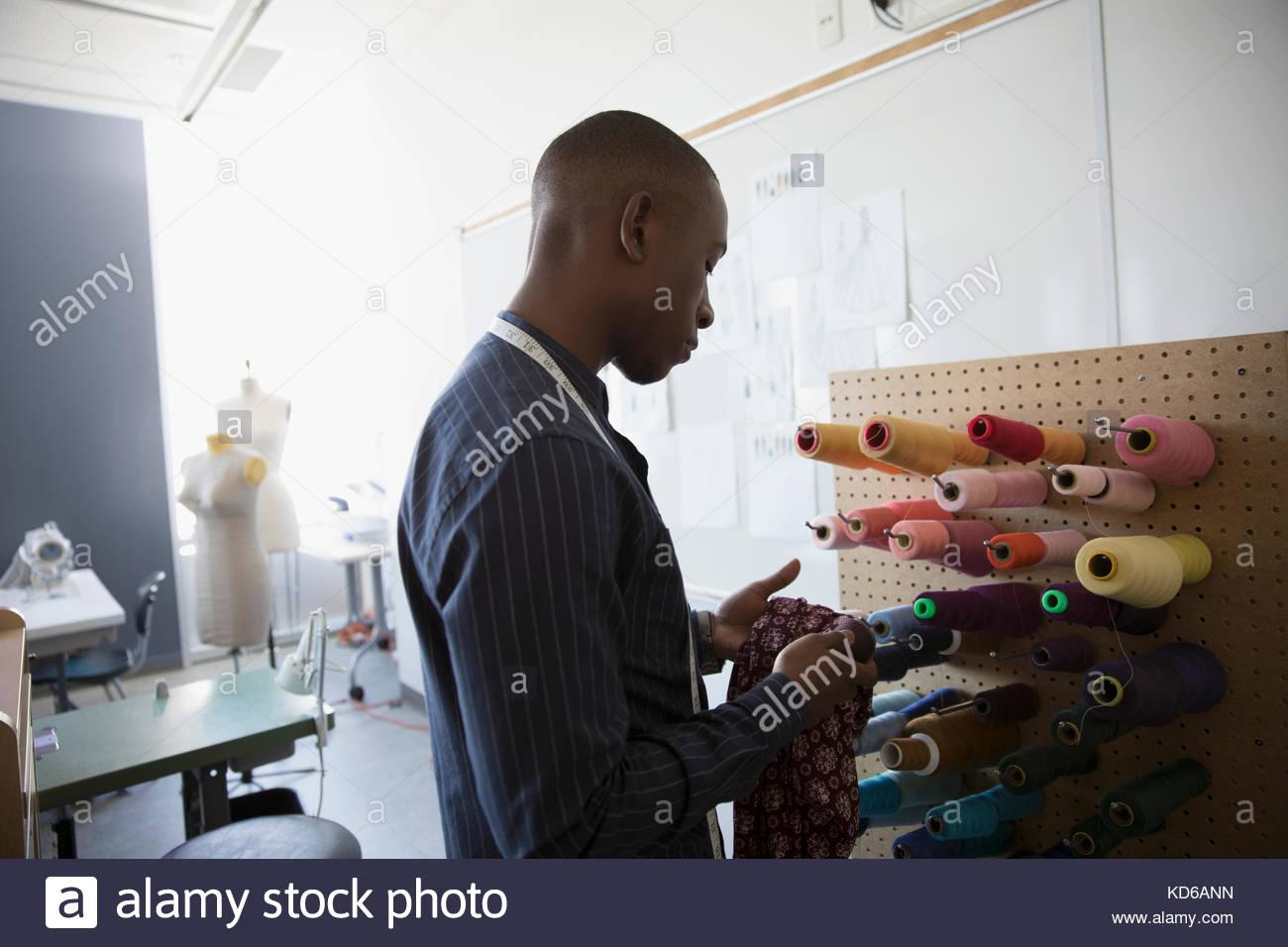 Male fashion designer at peg board with spools of multicolor thread in studio - Stock Image