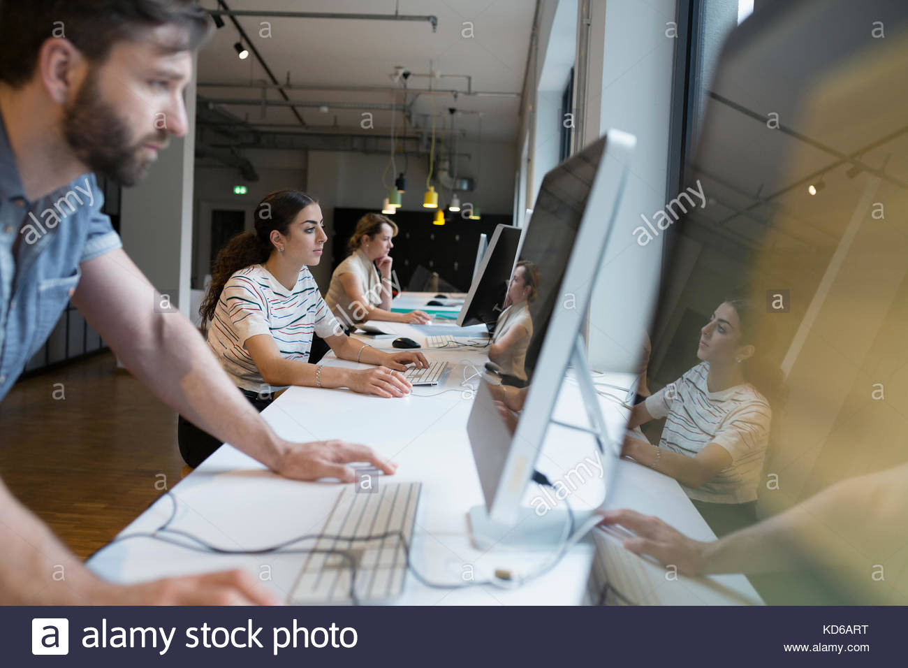 Business people using computers at counter in open plan office - Stock Image