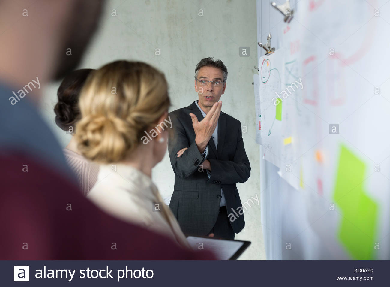 Business people brainstorming at board in office meeting - Stock Image