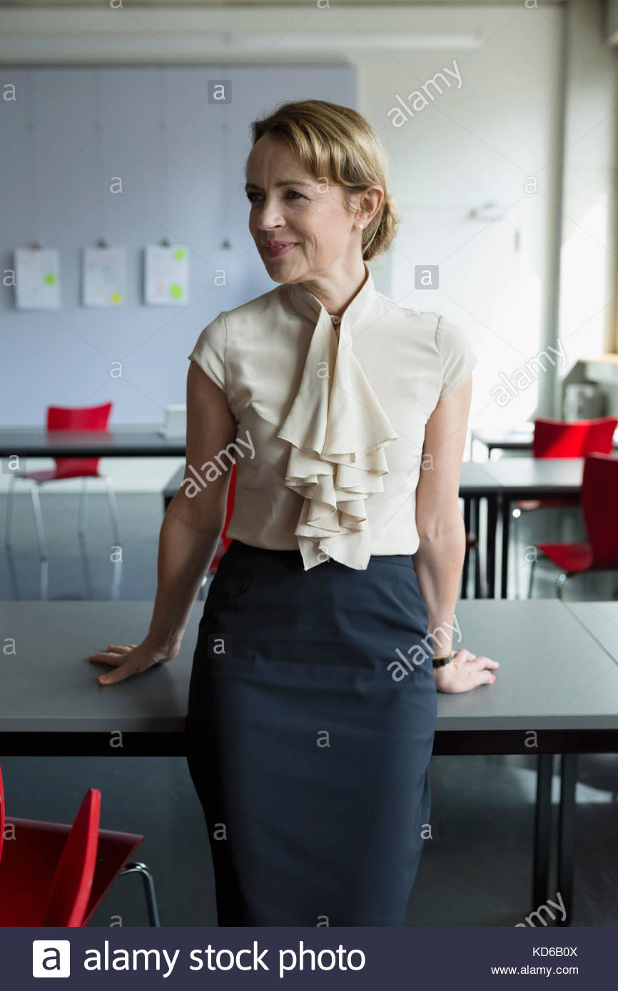 Portrait smiling female professor looking away in classroom - Stock Image