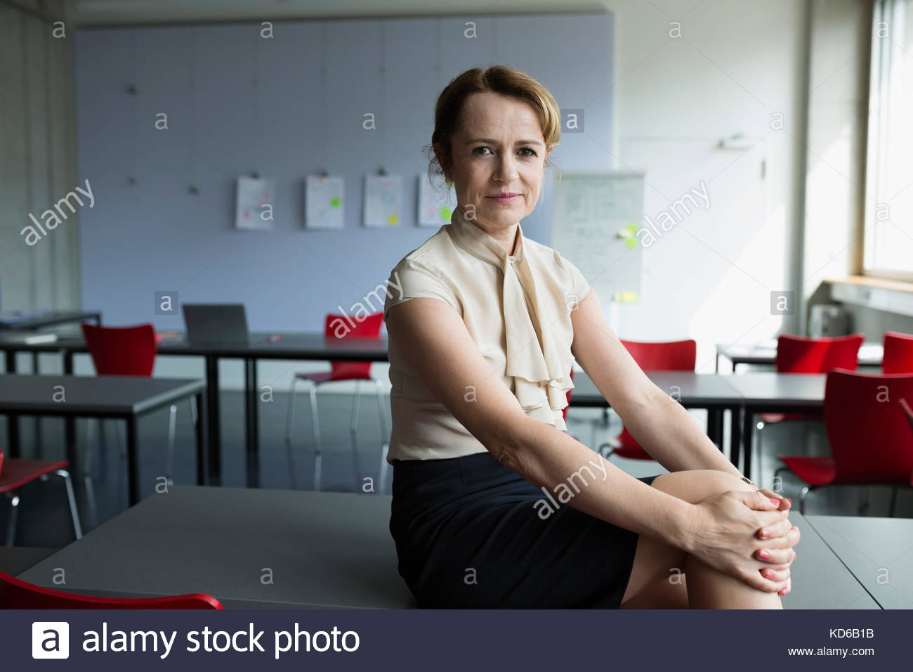 Portrait confident female professor in classroom - Stock Image
