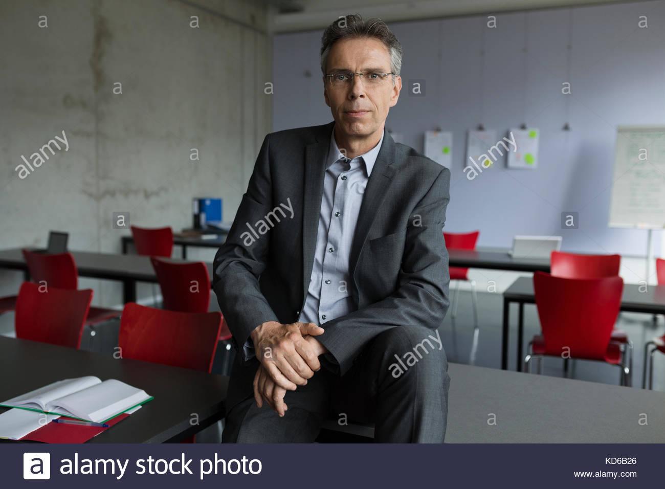 Portrait confident male professor in classroom - Stock Image