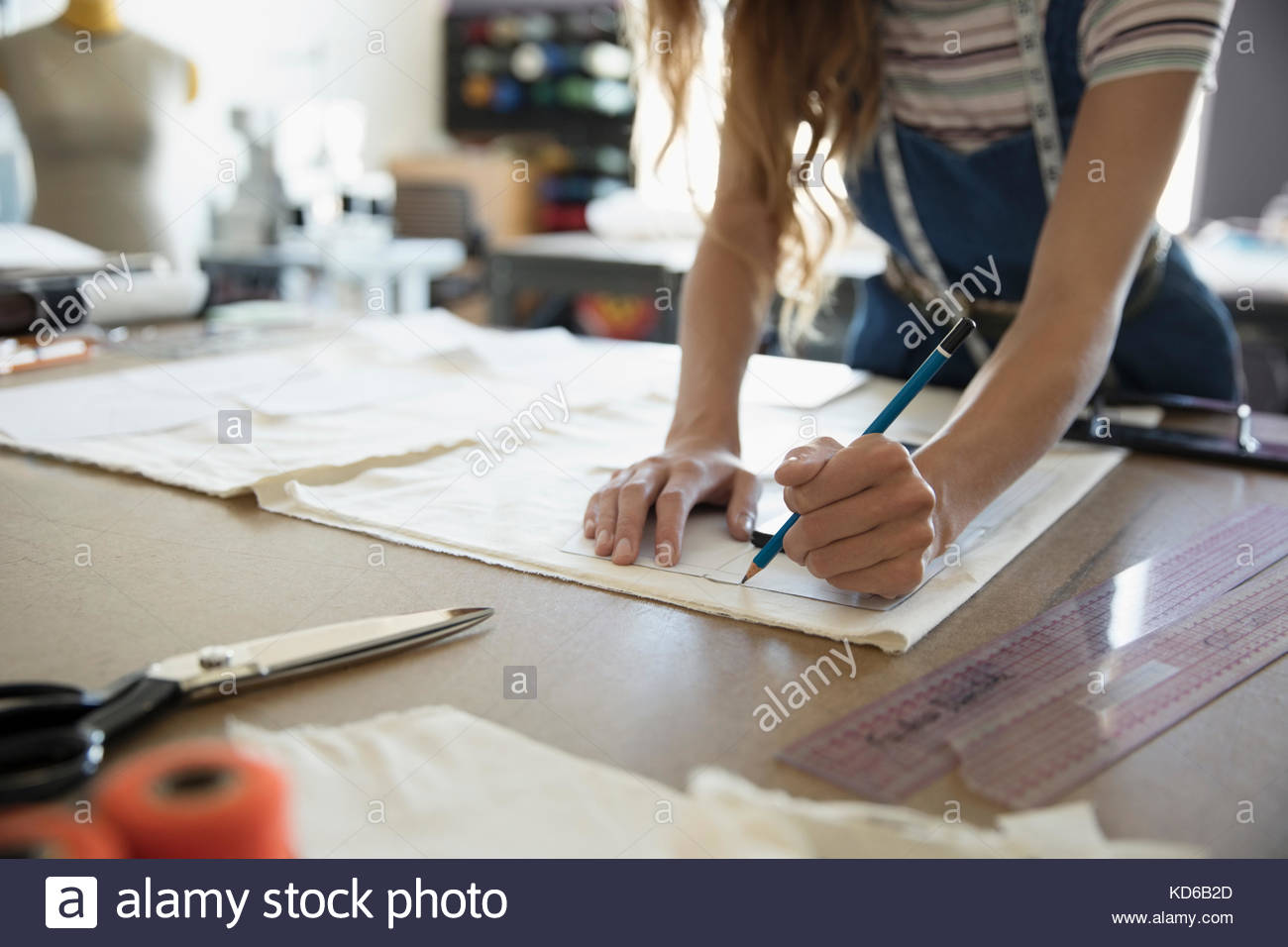 Female fashion designer tracing sewing pattern at workbench - Stock Image