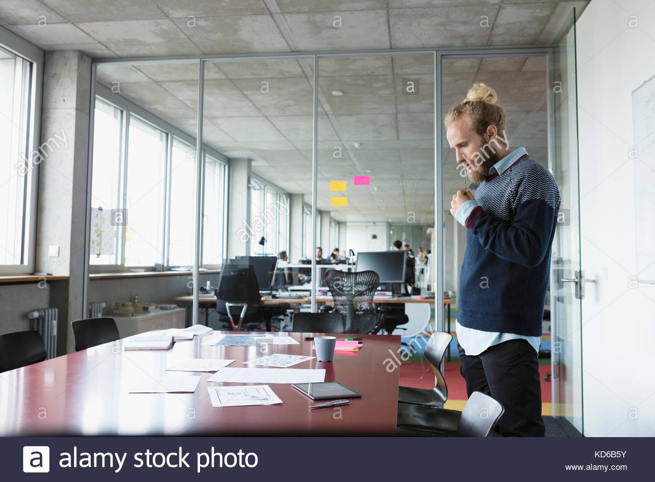 Focused male architect reviewing blueprints in conference room - Stock Image