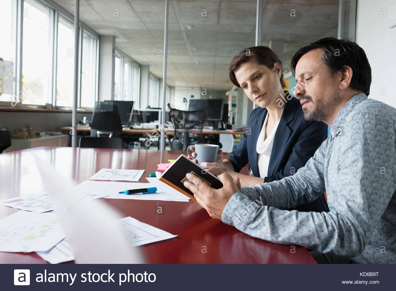 Business people reviewing paperwork and notes in conference room meeting - Stock Image
