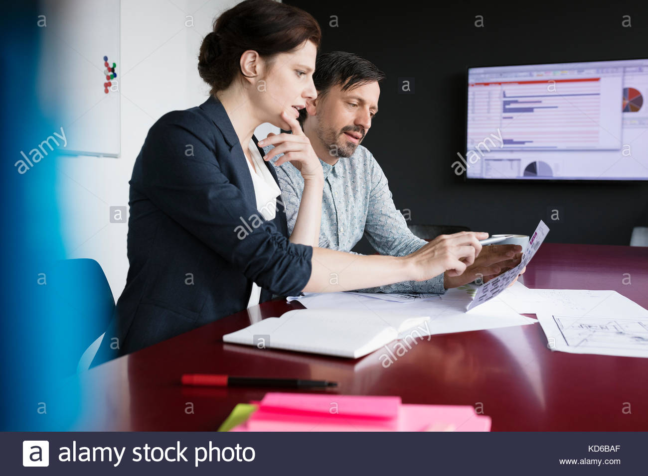 Business people reviewing paperwork in conference room meeting - Stock Image