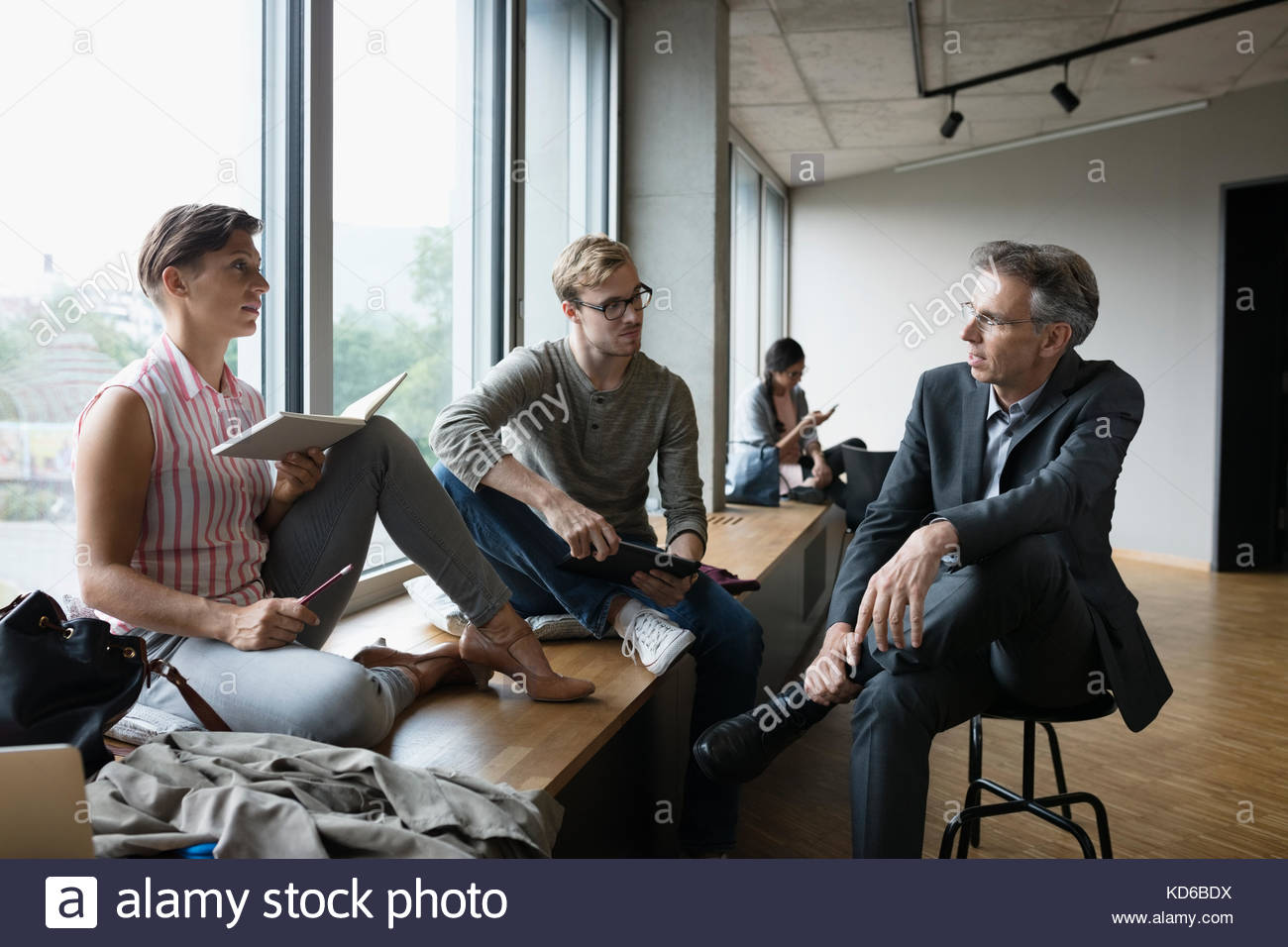 Professor talking to mature students in student lounge - Stock Image