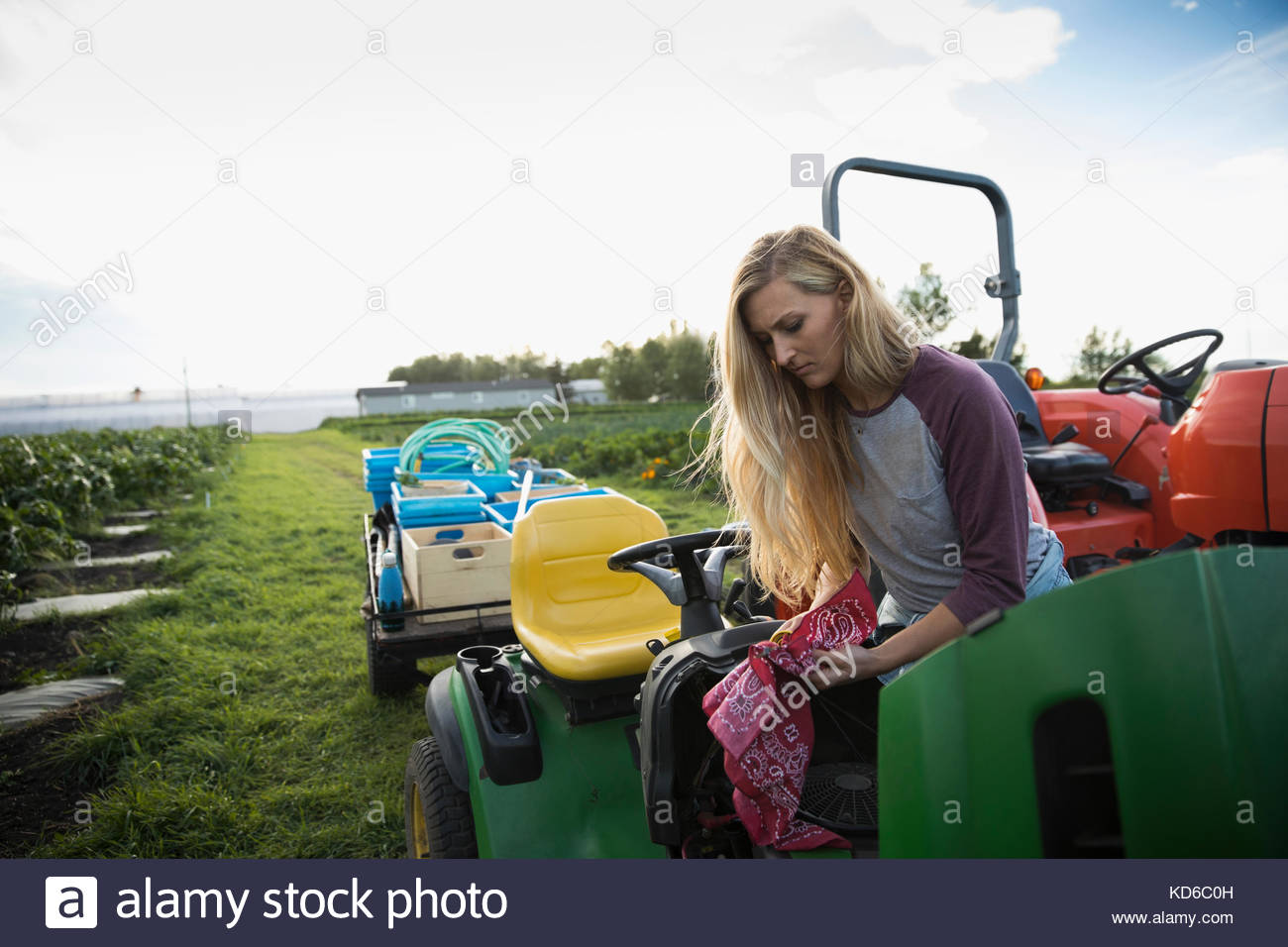 Female farmer with handkerchief on tractor on farm - Stock Image