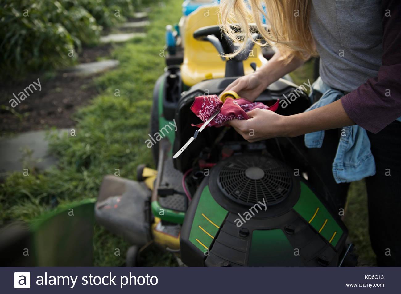 Female farmer checking oil dipstick at tractor - Stock Image