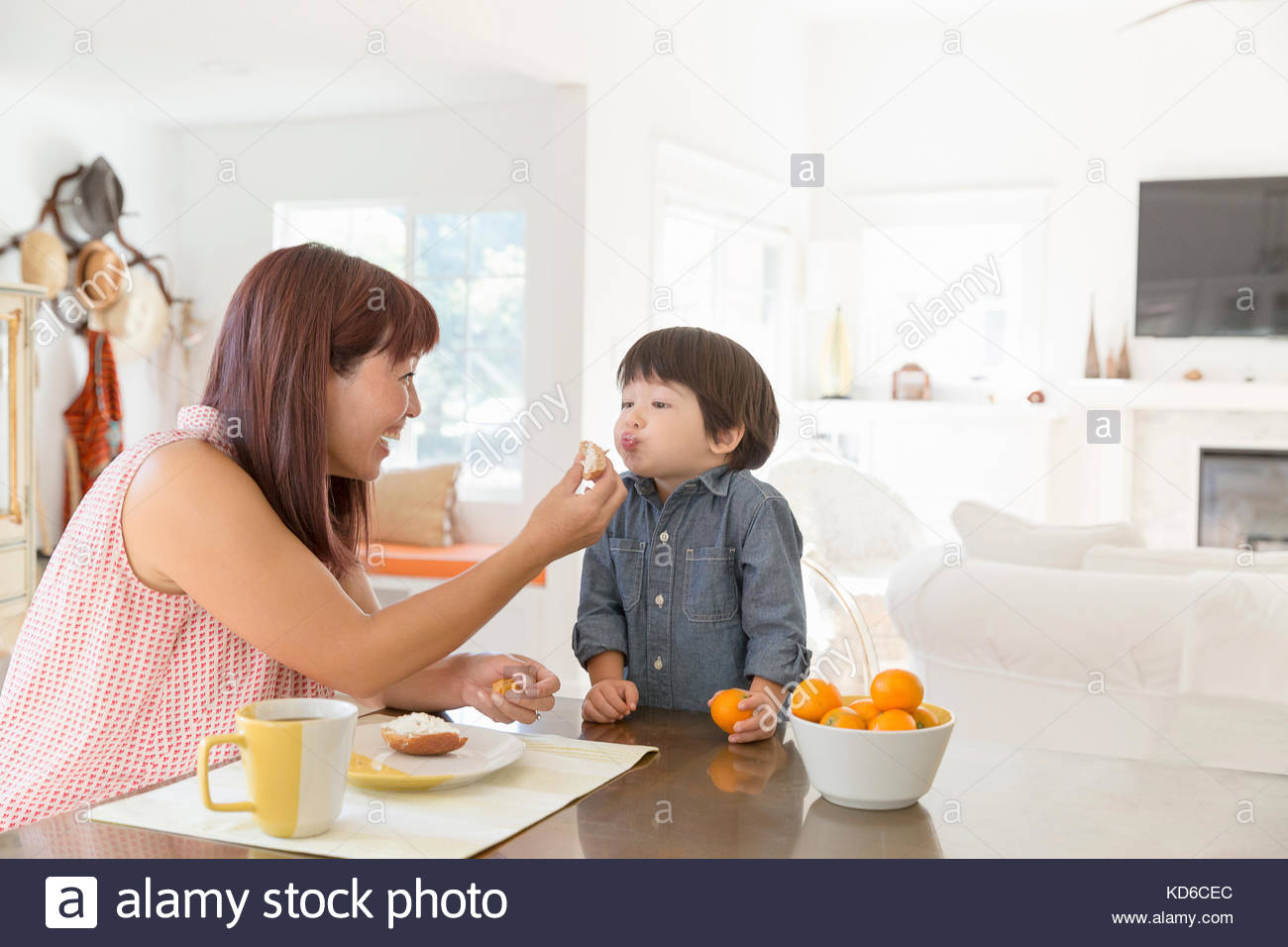 Mother feeding son at dining table - Stock Image