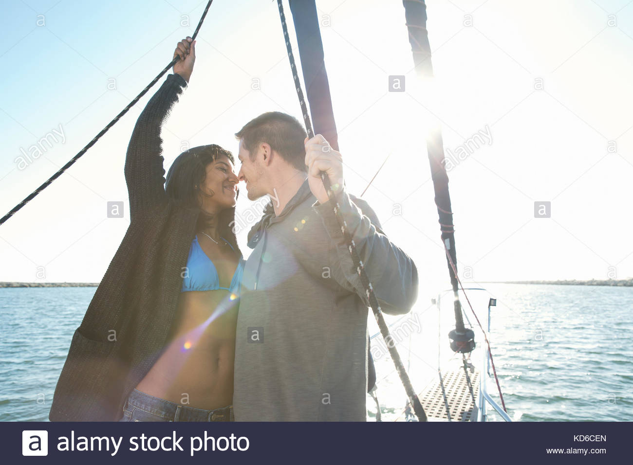 Affectionate couple kissing on sailboat on sunny ocean - Stock Image
