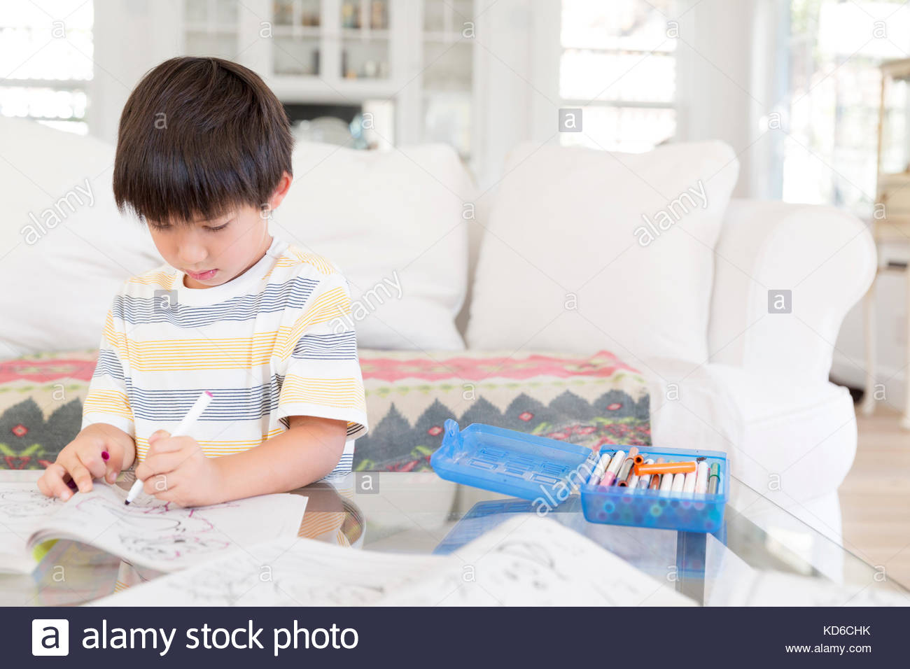 Boy coloring with markers and coloring book in living room ...