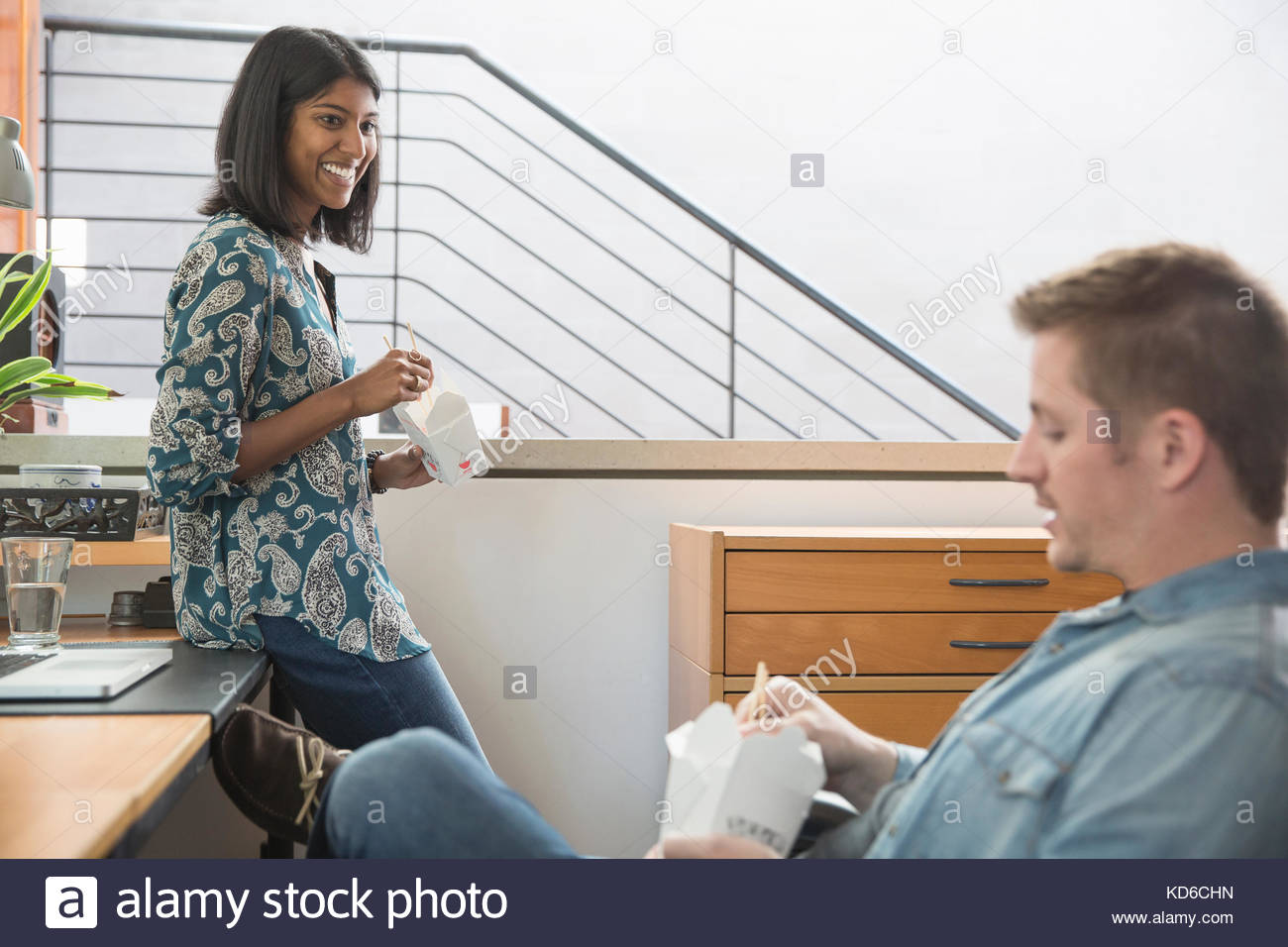 Couple eating Chinese takeout food in home office - Stock Image