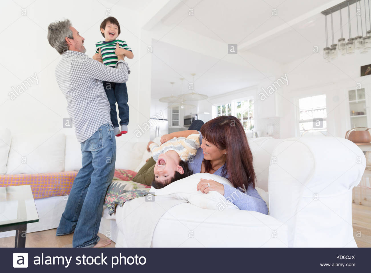 Playful family laughing and tickling in living room - Stock Image