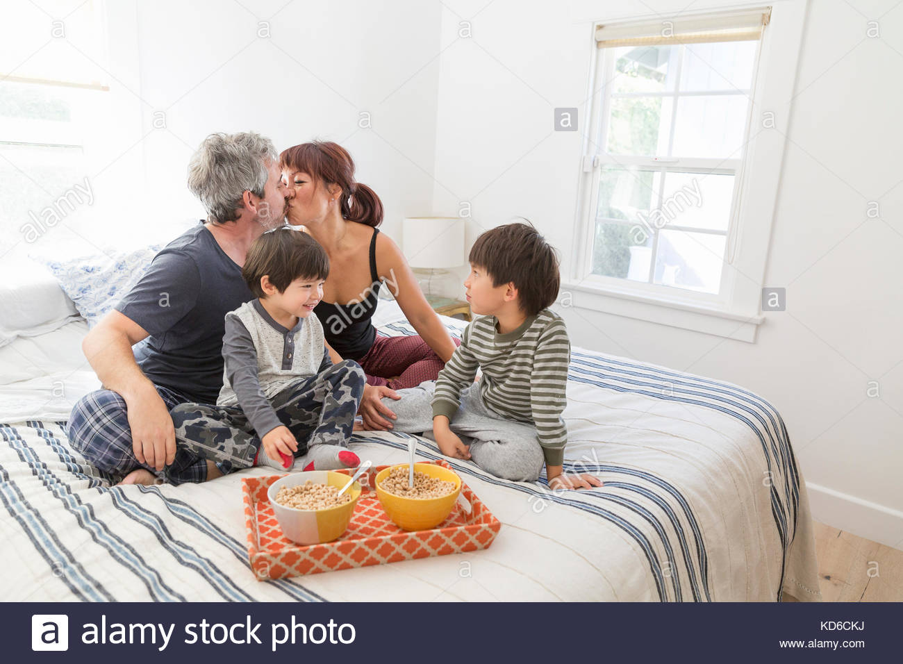 Young family eating breakfast in bed - Stock Image
