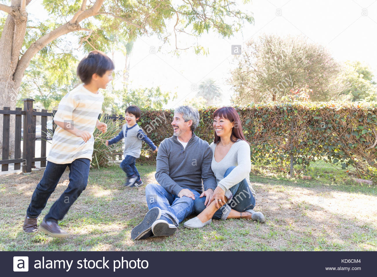 Happy young family sitting and playing in grass - Stock Image