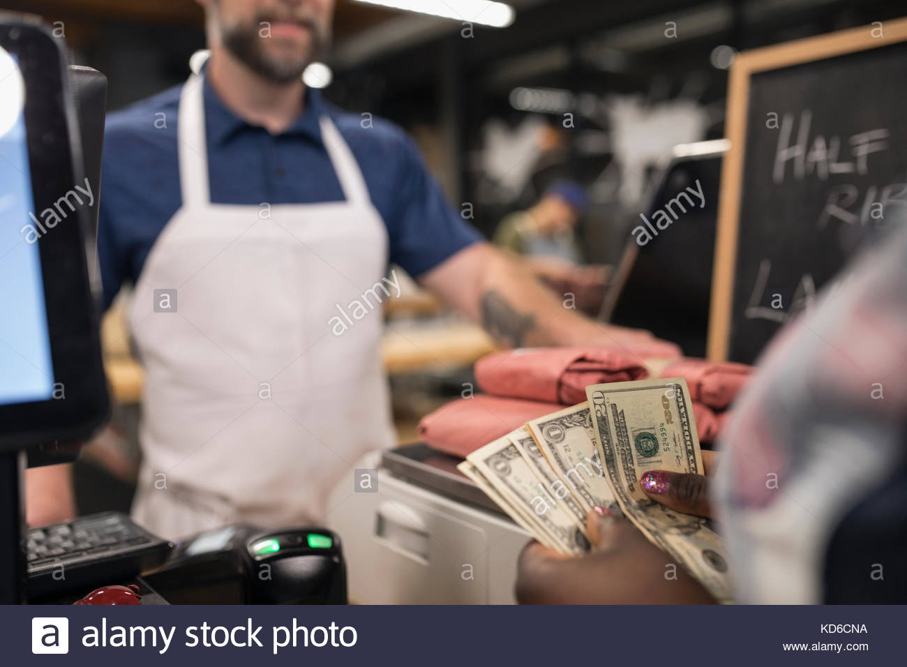 Customer with cash paying butcher in butcher - Stock Image