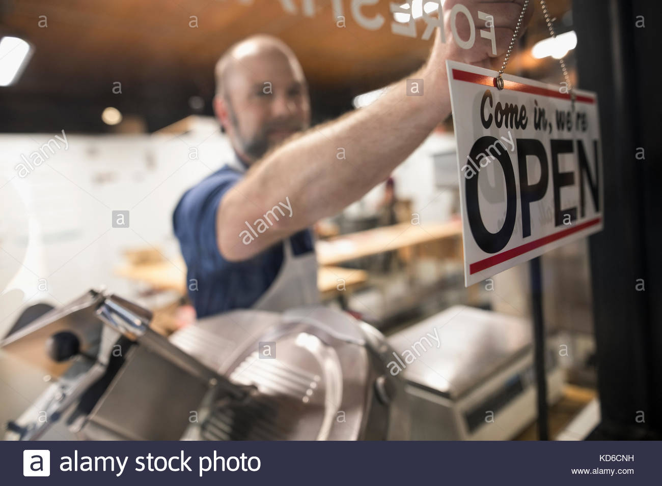 Male butcher changing open sign in butcher shop window - Stock Image