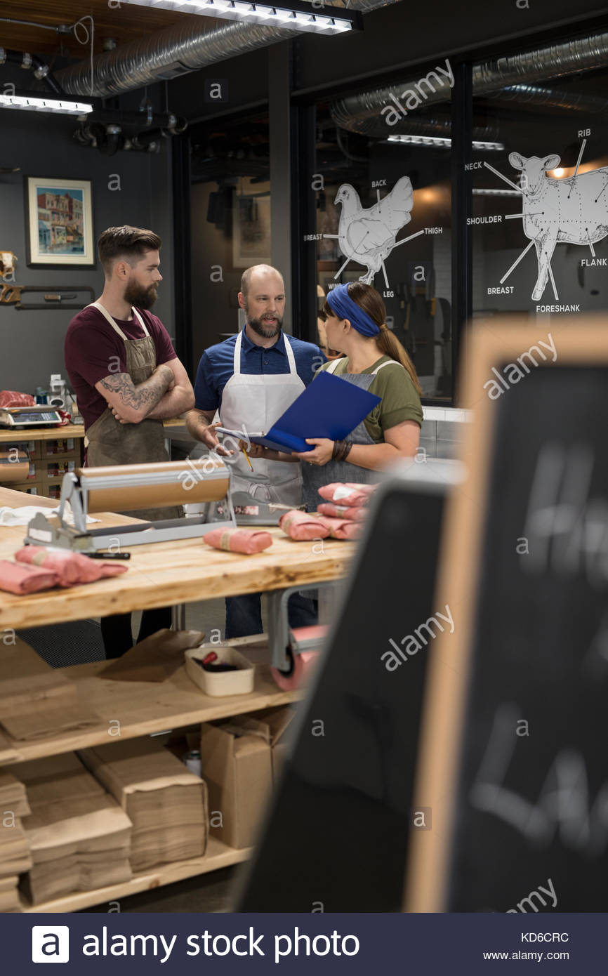 Butchers discussing paperwork in butcher - Stock Image