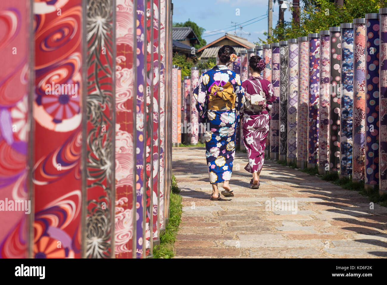 Arashiyama, Kyoto, Japan - September 18 2017: Two woman with kimonos walk through poles with traditional colourful Stock Photo