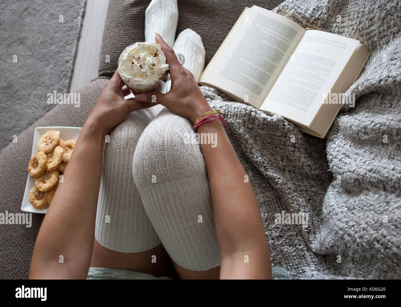 closeup of woman reading book at home on couch with hot chocolatemilk and cookies Stock Photo