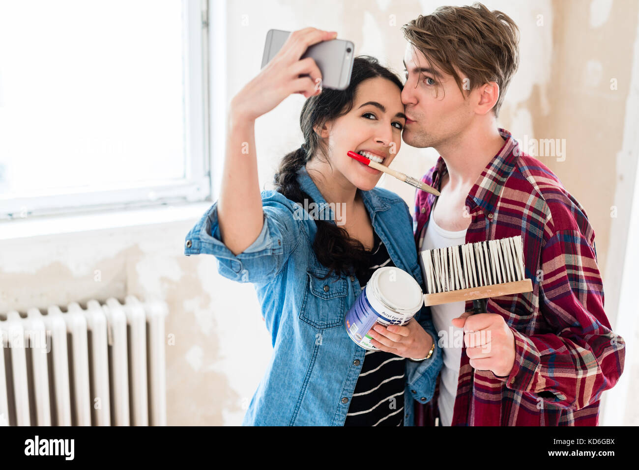 Young couple making a selfie while working to the renovation of  - Stock Image