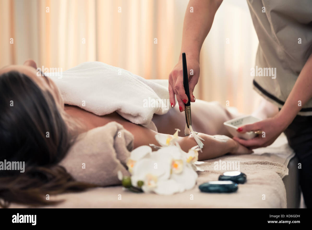 Woman lying down during Asian anti-aging treatment - Stock Image