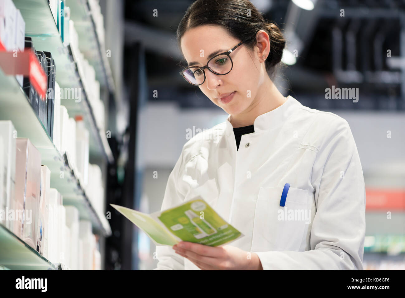 Low-angle portrait of female pharmacist checking the medical pre - Stock Image
