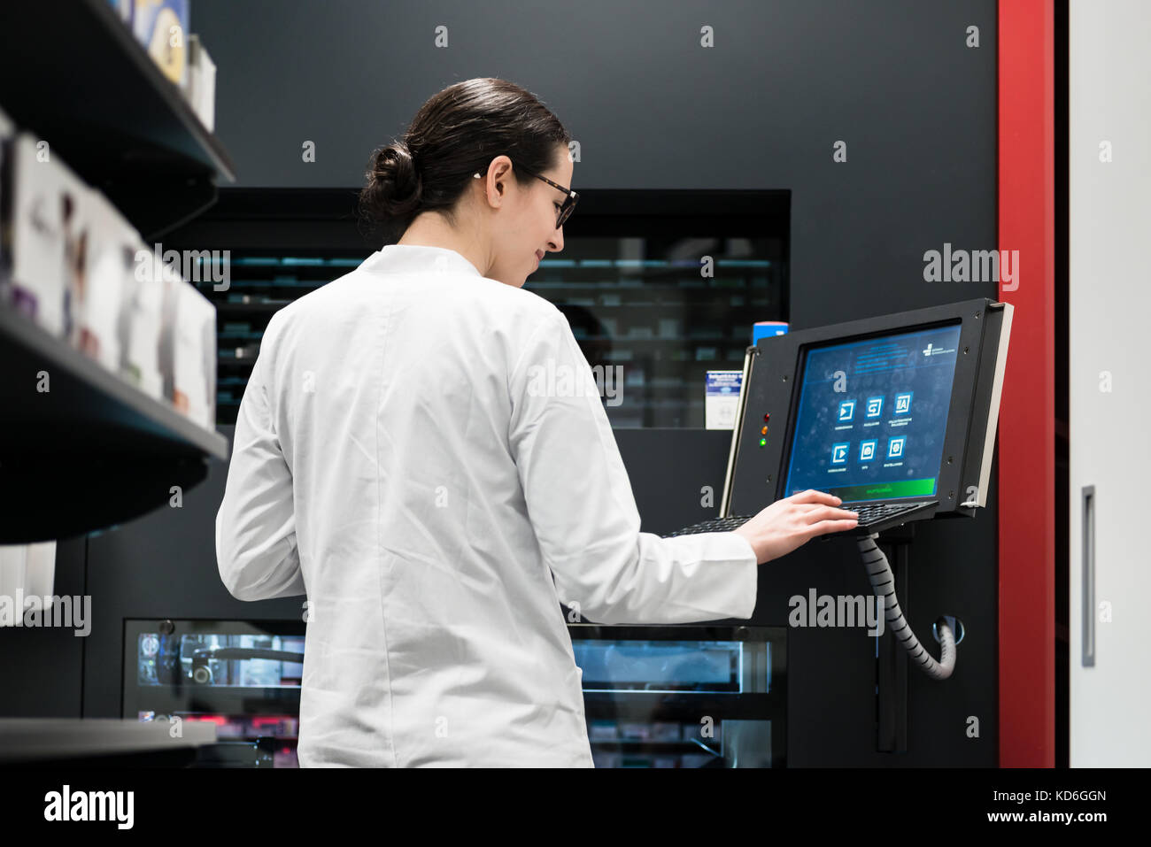 pharmacist using a computer while managing the drug stock in pha - Stock Image