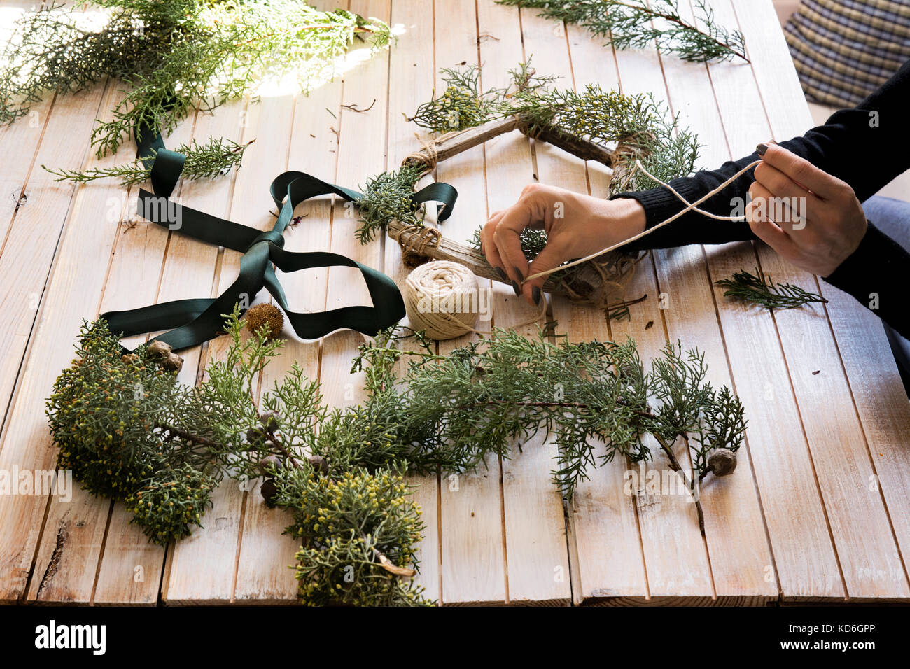 Florist at work: Creating a wooden wreath with red barries, surrounded by the arts and crafts. - Stock Image
