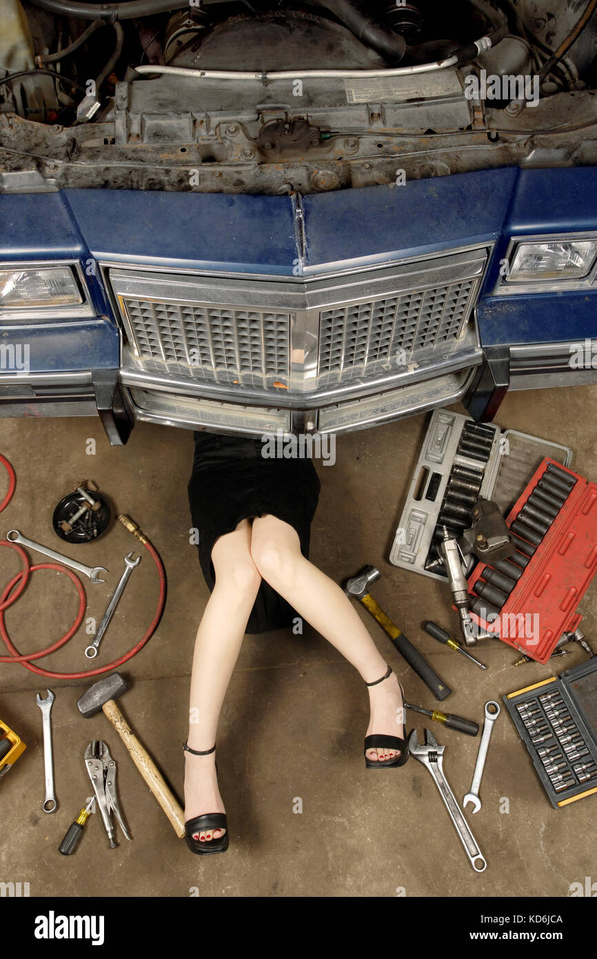 Photo of a woman wearing a black skirt and heels doing repairs under the front of an old car from the early 80's. - Stock Image