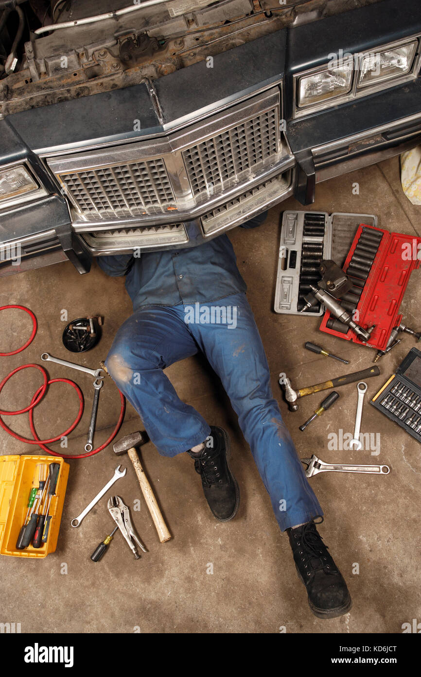 Photo of a mechanic doing repairs under the front of an old car from the early 80's. - Stock Image