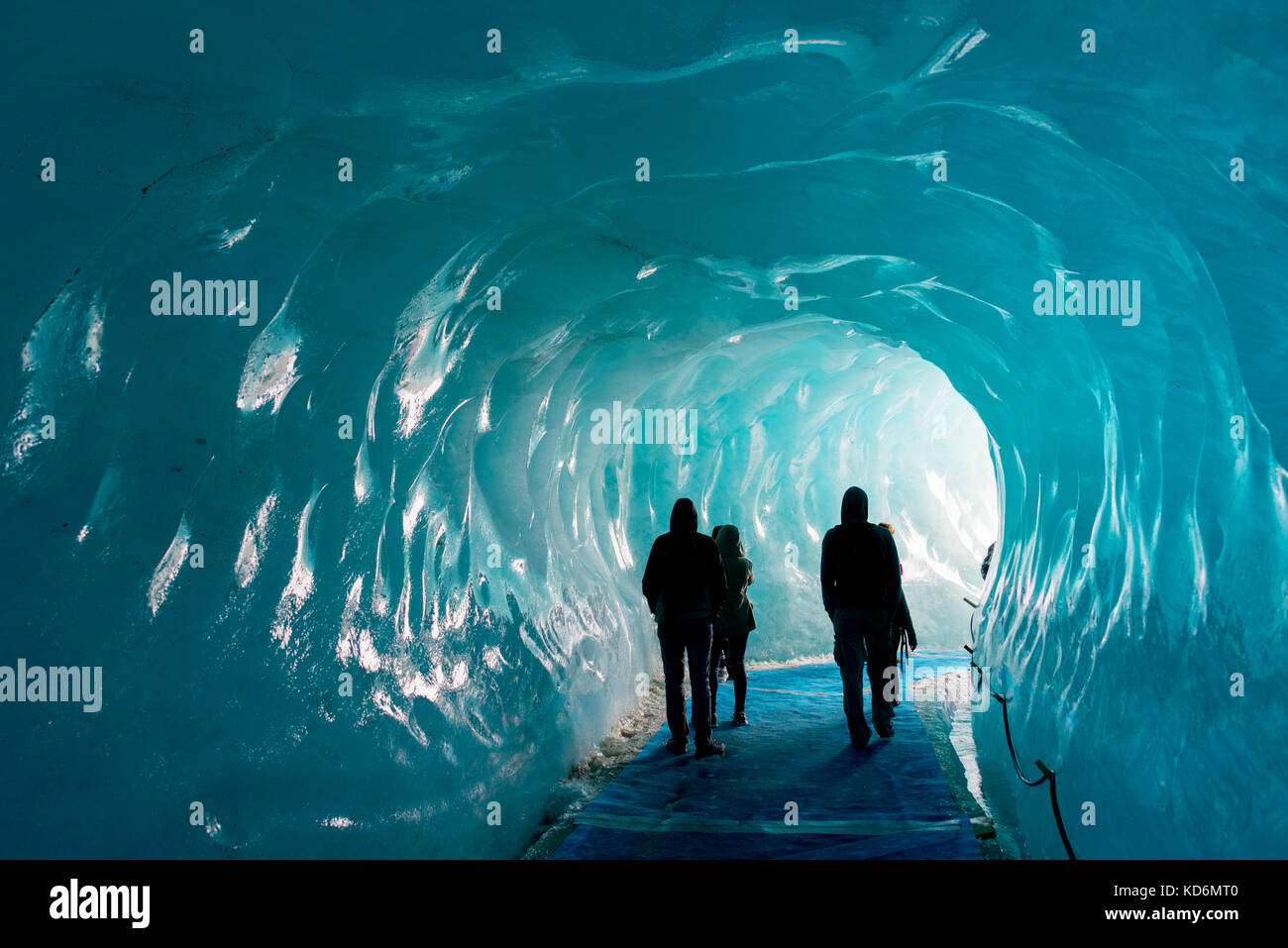 Silhouettes of people visiting thee ice cave of the Mer de Glace glacier,  in Chamonix Mont Blanc Massif, The Alps, - Stock Image