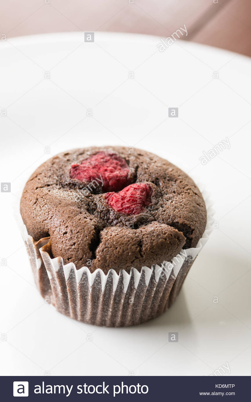 Chocolate cup cake muffin with raspberries isolated on the white plate. - Stock Image