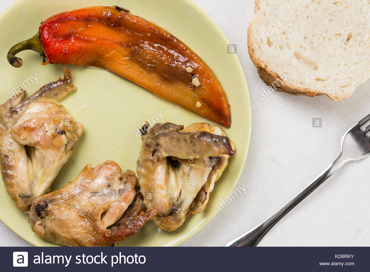 Flat lay above fried chicken wings with fried paprika served on the plate with bread and fork. Stock Photo