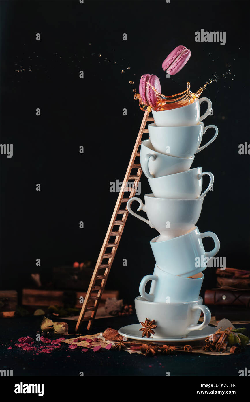 Tower of white coffee cups with a ladder, macaroons, splash and coffee drops on a dark background. Indulgence concept. - Stock Image
