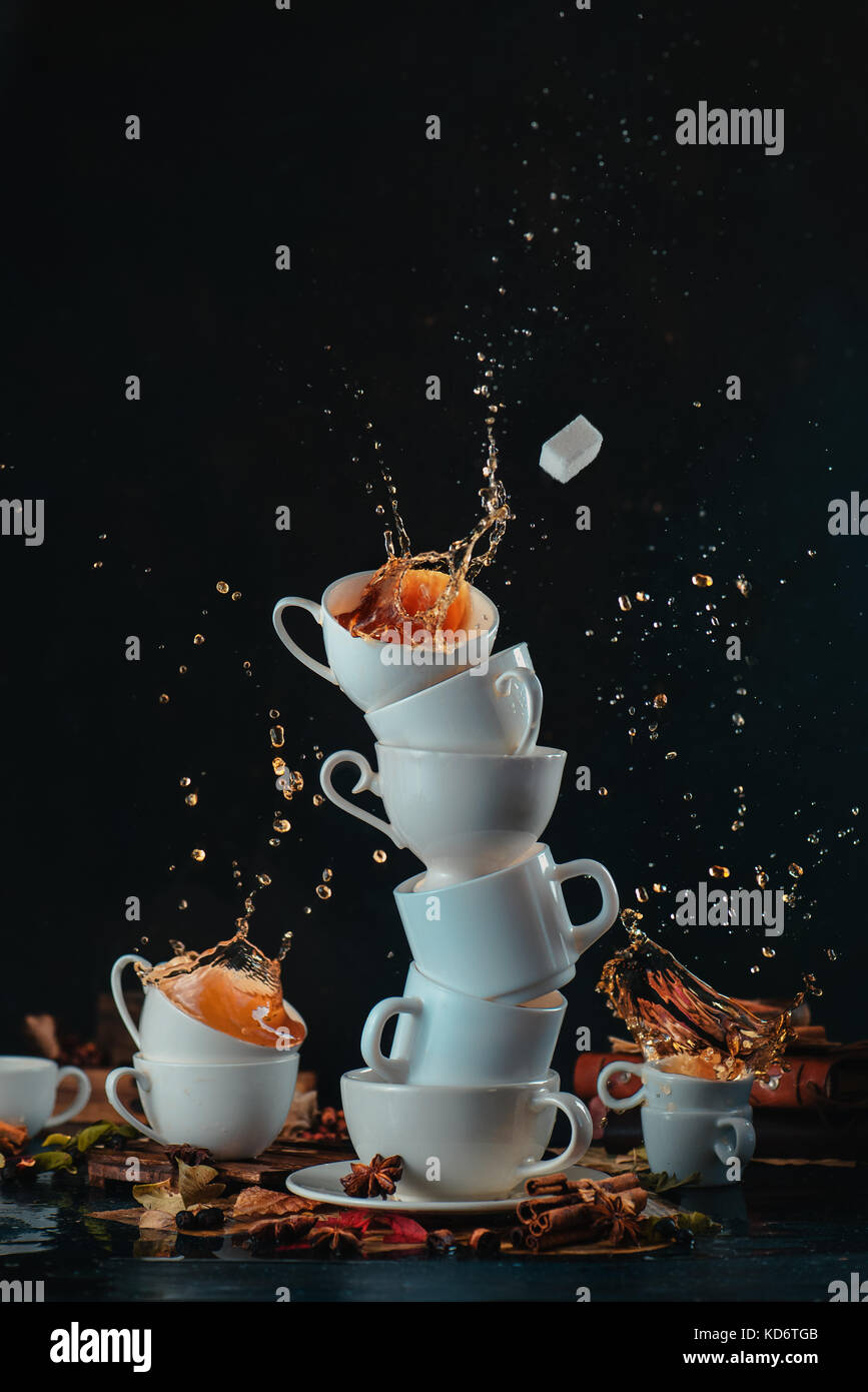 Stack of white coffee cups with dynamic splashes and coffee drops on a dark background. Kitchen mess and mad tea - Stock Image