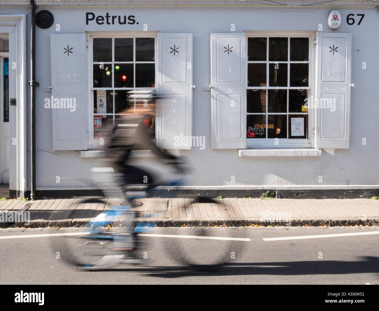 The Petrus Designer clothes shop in Cambridge uk, an independent store. With a passing cyclist with motion blur. - Stock Image