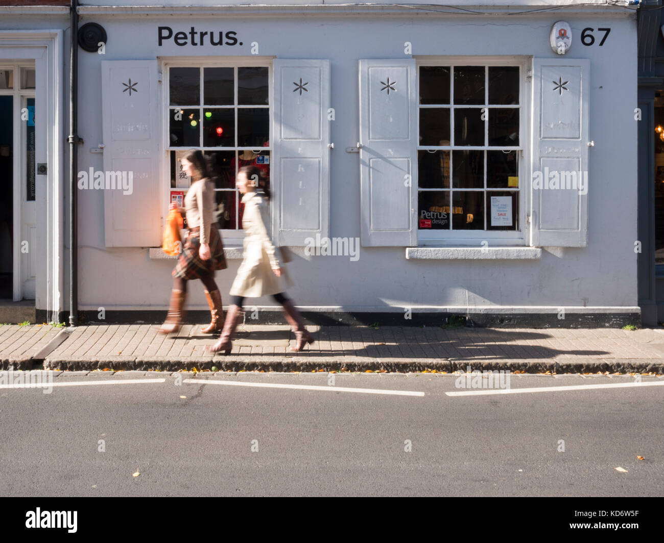 The Petrus Designer clothes shop in Cambridge uk, an independent store. With a passing shoppers with motion blur. - Stock Image