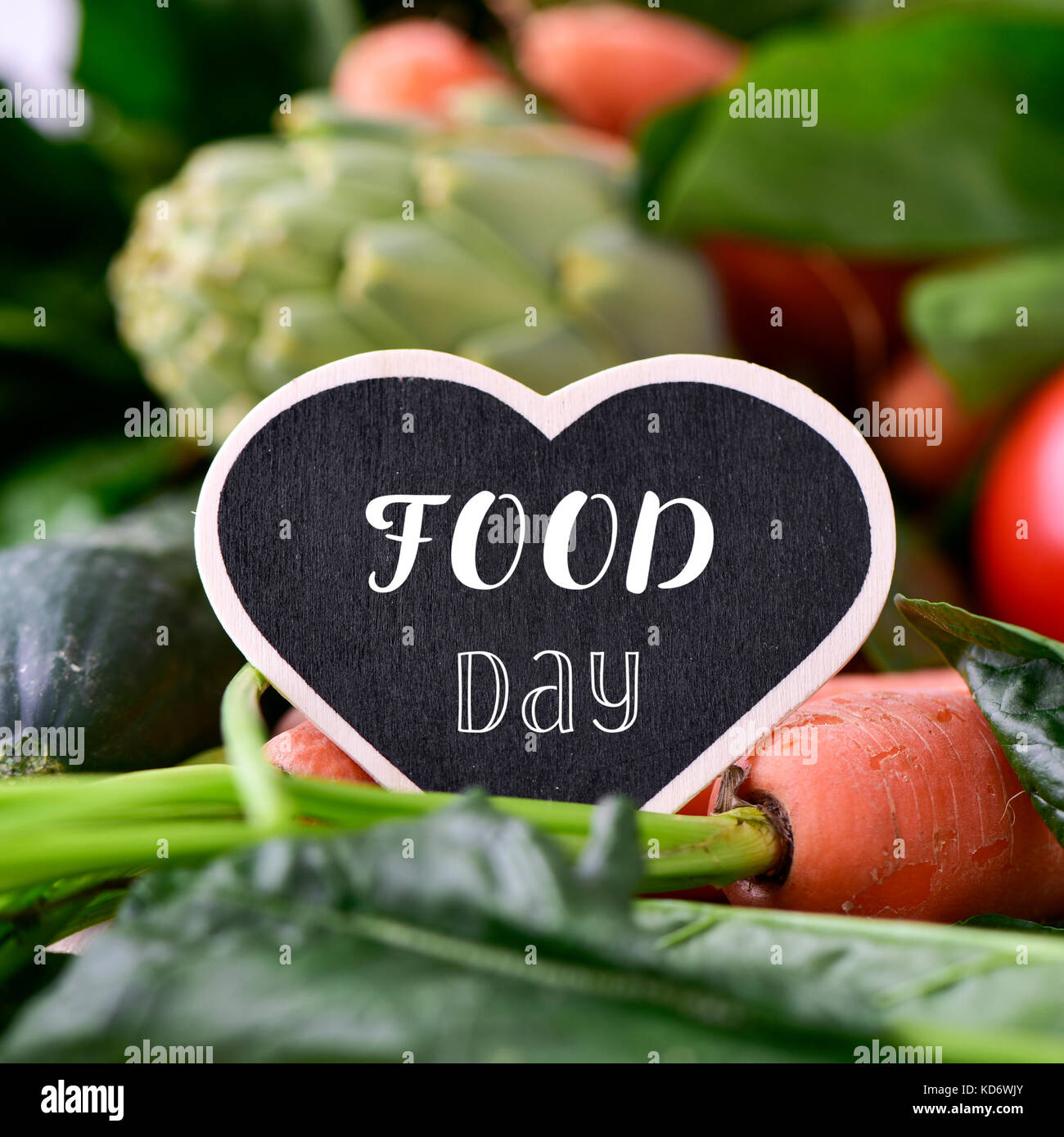 closeup of a heart-shaped chalkboard with the text food day placed on a pile of some different raw vegetables, such - Stock Image