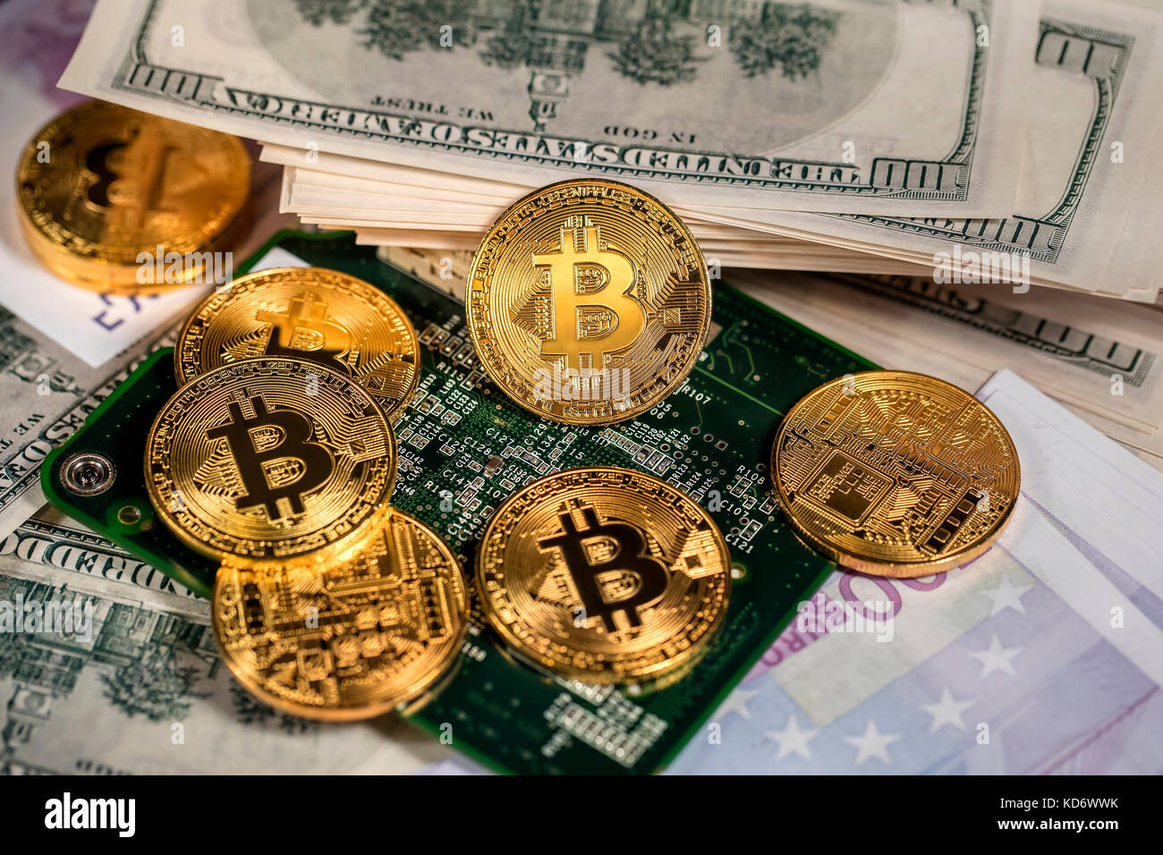 Closeup view of golden coins of Bitcoin on hundred dollars bills. - Stock Image