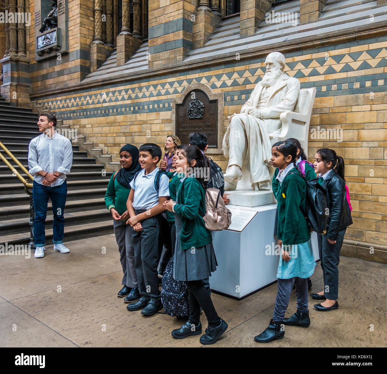 Schoolchildren on a school trip, posing for a photograph in front of the Charles Darwin statue, at the Natural History - Stock Image