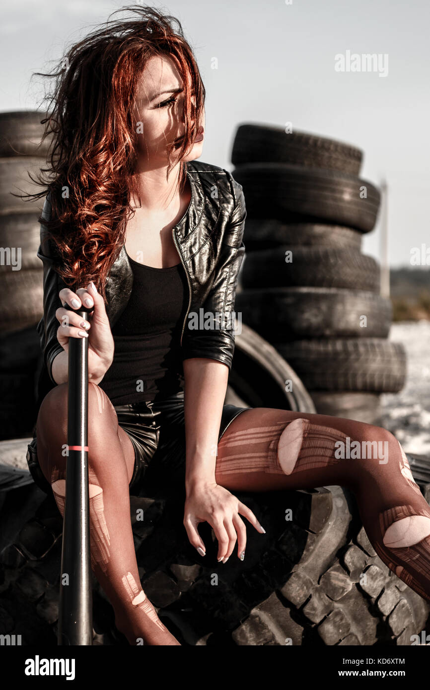 Disheveled redhead woman sitting with a baseball bat at the background of an old tires - Stock Image