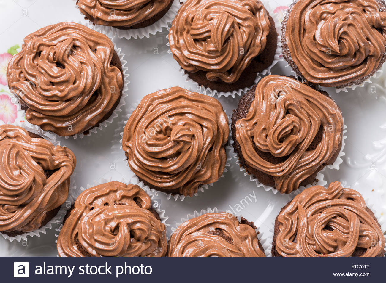 Flat lay above full plate of chocolate cup cakes with ganache chocolate cream. - Stock Image