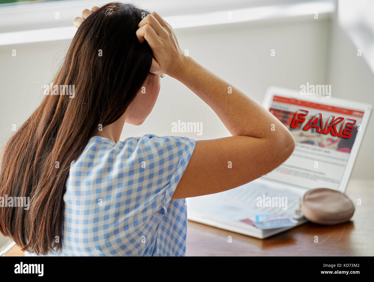 Woman realising she has used a fake website - Stock Image
