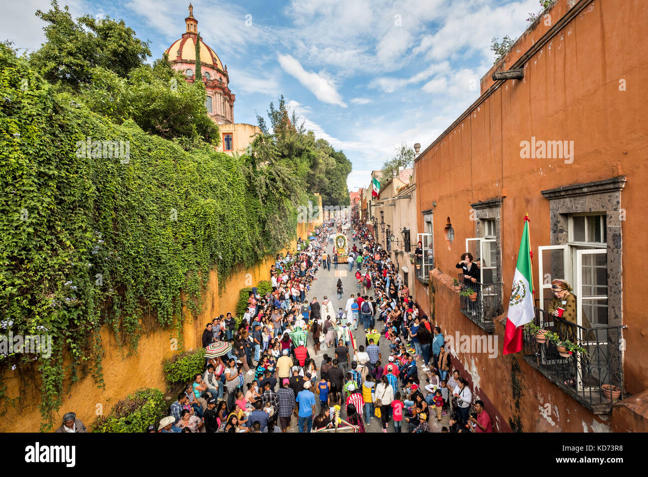A religious procession carries a statue of St Michael through the historic district during the week long fiesta - Stock Image