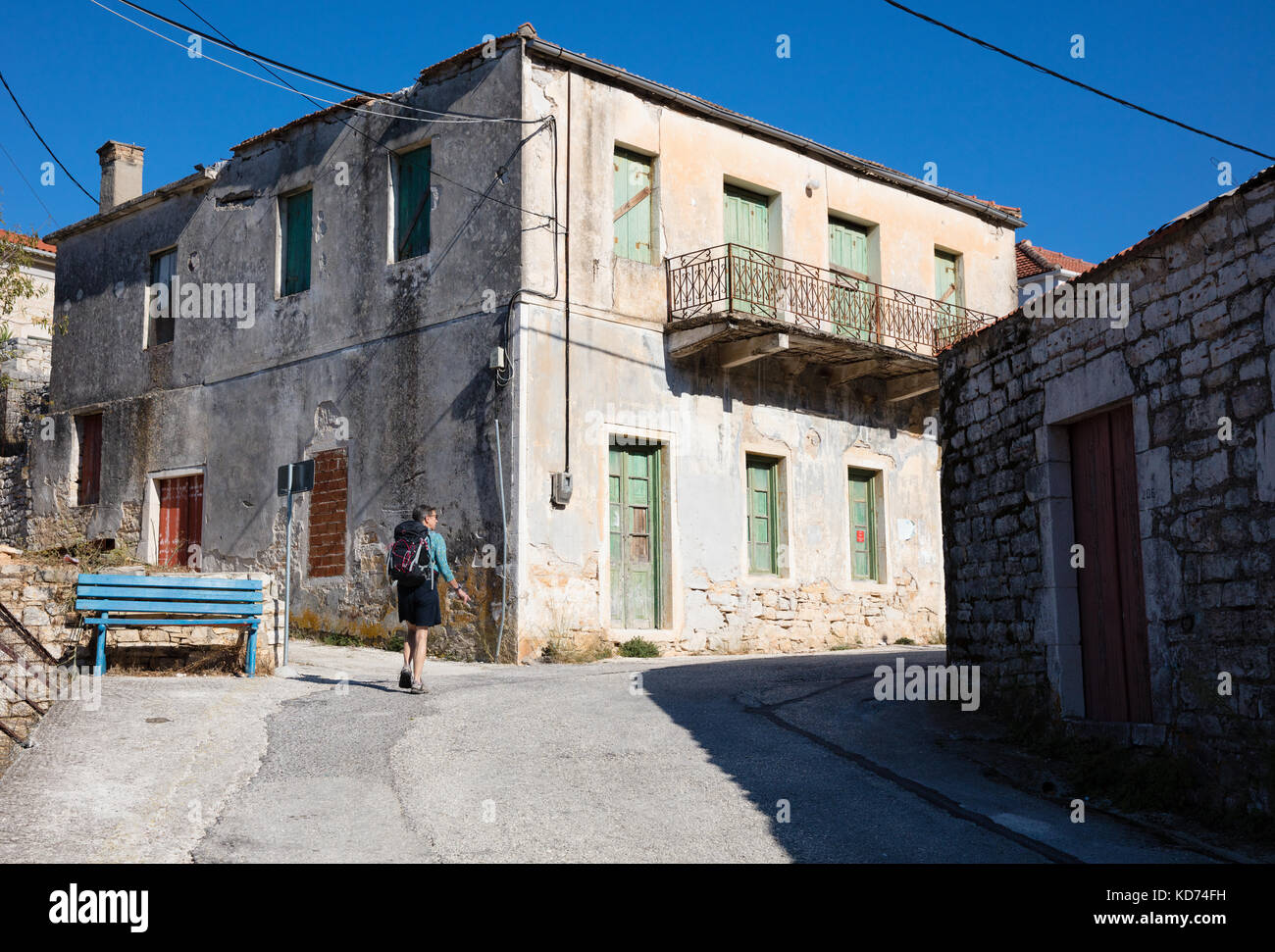 A female hiker walking past abandoned houses along a steep street in the village of Kioni on Ithaka in the Greek - Stock Image